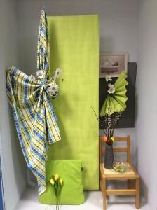 Lente gevoel creëren met behangpapier , linnen en woning decoratie. Groene behangpapier ophangen aan het plafond met 2 nietjes en nylondraad. Links en rechts een nietje , nylondraad langs beide kanten er door steken en gelijk trekken. Linnen, een deel voor het behang hangen. Als je het niet doet, geeft het geen mooi opvul effect. Uitvalhoek altijd naar de buitenkant. Decoratie materiaal altijd recht hangen en recht zetten, nooit schuin. Want anders komt het niet netjes over.